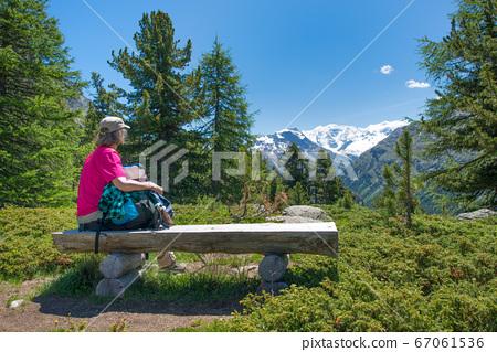 An elderly woman rests during an alpine trek 67061536