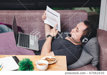 Young man lying on the couch and video call with colleagues by laptop in home office. 67062630