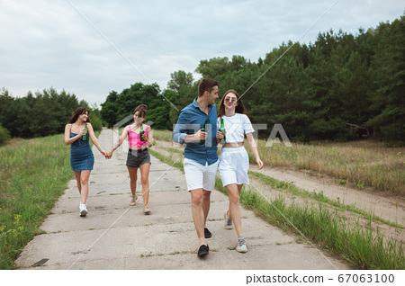 Group of friends clinking beer bottles during picnic in summer forest. Lifestyle, friendship 67063100