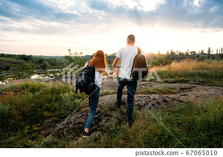 Local travel, Solo Explorers, Small Group tourist. Young couple going for hiking, walk in nature. Summer Outdoor Activities. Caucasian hiker couple enjoying themselves on summer vacation 67065010