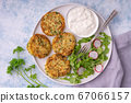 Zucchini fritters served with yogurt dip. 67066157