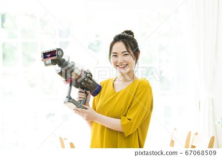 젊은 여성 청소기 카메라 시선 67068509