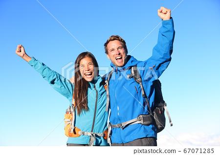 Happy hiking couple cheering 67071285