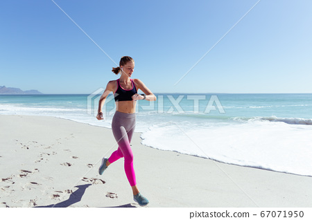 Woman checking time while running on the beach 67071950