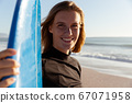 Portrait of smiling woman with surfboard at the beach 67071958