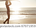 Woman with surfboard walking on the beach 67071959