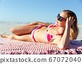 Beautiful woman sunbathing on the beach 67072040