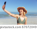 Woman smiling while taking a selfie on the beach 67072049