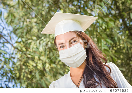 Female Graduate in Cap and Gown Wearing Medical Face Mask 67072683