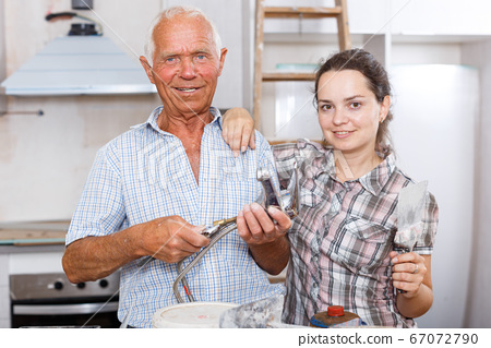 Cheerful woman with elderly father during overhaul 67072790