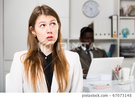 Upset woman and man colleague working with laptop on background in office 67073148