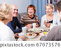 Smiling aged friends are sitting at table with tea and talking about life 67073576