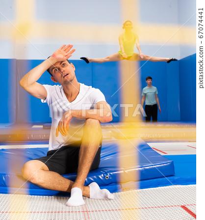 Tired guy sitting on trampoline 67074441