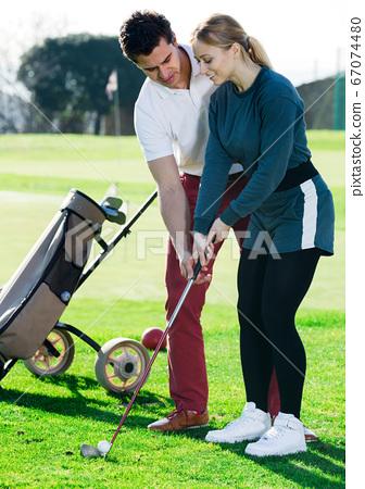 Golf trainer teaches a woman game 67074480