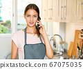 Woman talking on smartphone at kitchen 67075035