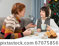 Two women drink tea and eat cakes near the New Year tree. Mother with daughter 67075856