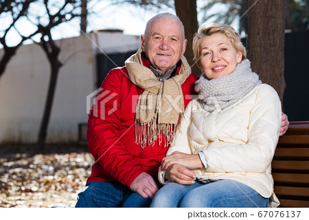 Mature couple sitting in park 67076137
