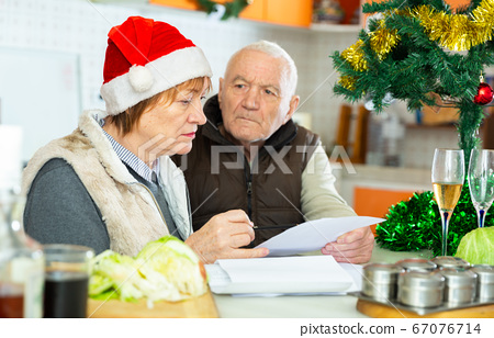 Aged family trying to pay utility bills before new year dinner 67076714