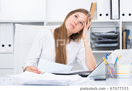 Upset young businesswoman in office 67077555