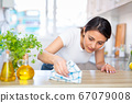 Young latino woman cleans the kitchen table 67079008