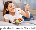 Peruvian housewoman eating vegetable salad on sofa at home 67079140