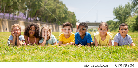 Portrait of smiling children who are posing lying in park 67079504