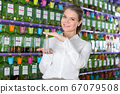 Female seller showing perfume 67079508