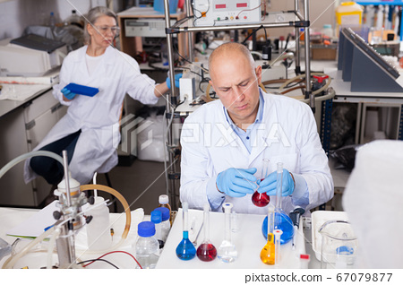 Lab technician working with reagents 67079877
