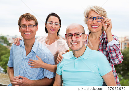 Portrait of smiling mature people in glasses outdoors together 67081072