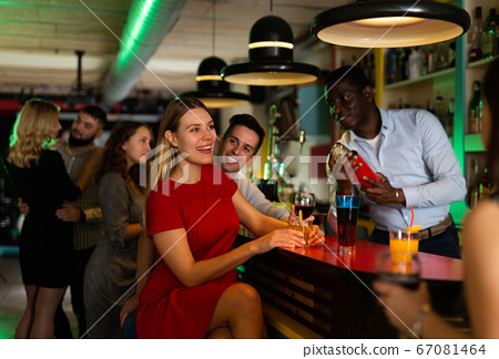 Man bartender making alcohol cocktail for couple in nightclub 67081464