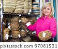 customer standing with wicker basket 67081531