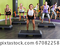 athletic girls during workout in gym with barbell 67082258