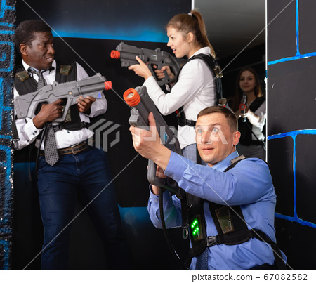 Men and women in business suits playing laser tag emotionally in dark room 67082582