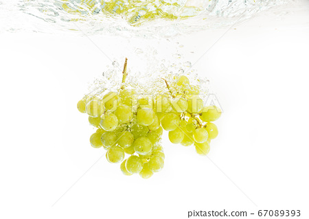 Bunch of green grapes splashing into crystal clear 67089393