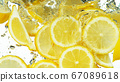 Lemon Slices falling deeply under water on white 67089618