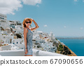 luxury beautiful girl in a glasses, in an expensive hotel on a tropical island, against a background of azure sea bay, on the terrace. Beautiful blond girl on Santorini Island Greece 67090656