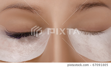 Eyelash Extension Procedure. Close up view of beautiful female eye with long eyelashes, smooth healthy skin. 67091805