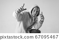 Black and white stylish modern epic portrait of bboy in a white hoodie on a white background. Breakdance and hiphop dancer. Mysterious and cool. 67095467