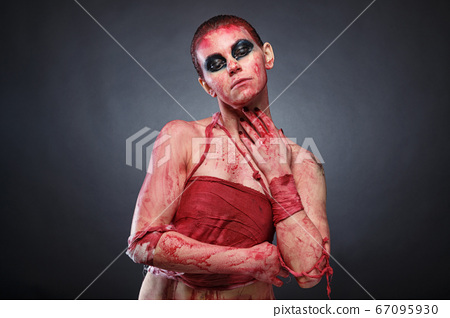 Horror photo of girl in fake blood on grey background 67095930