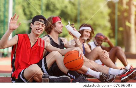 Asian player and his multinational team having rest on basketball arena outdoors, empty space 67096097