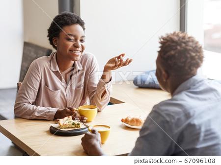 Joyful black couple having fun on first date at modern coffee shop 67096108