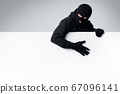 Masked thief holding white blank advertising board 67096141