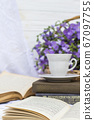 cup coffee (tea), books and bouquet flax in wicker basket 67097755