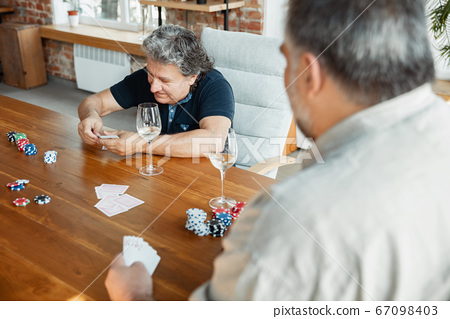 Two happy mature friends playing cards and drinking wine 67098403