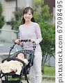 유모차를 눌러 주택가를 산책하는 어머니와 소년의 아기 67098495