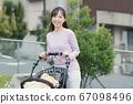 유모차를 눌러 주택가를 산책하는 어머니와 소년의 아기 67098496