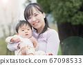 소년의 아기를 안는 미소 어머니 67098533