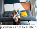 Beautiful bored brunette girl on the couch in a 67100615