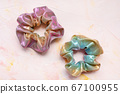 Two trendy holographic scrunchies on pink background 67100955