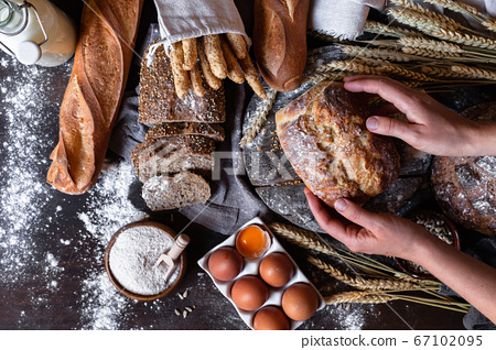 Concept of homemade bread, natural farm products, domestic production. Healthy and tasty organic food. Woman baked round whole grain bread. Top view flat lay, dark black background. 67102095